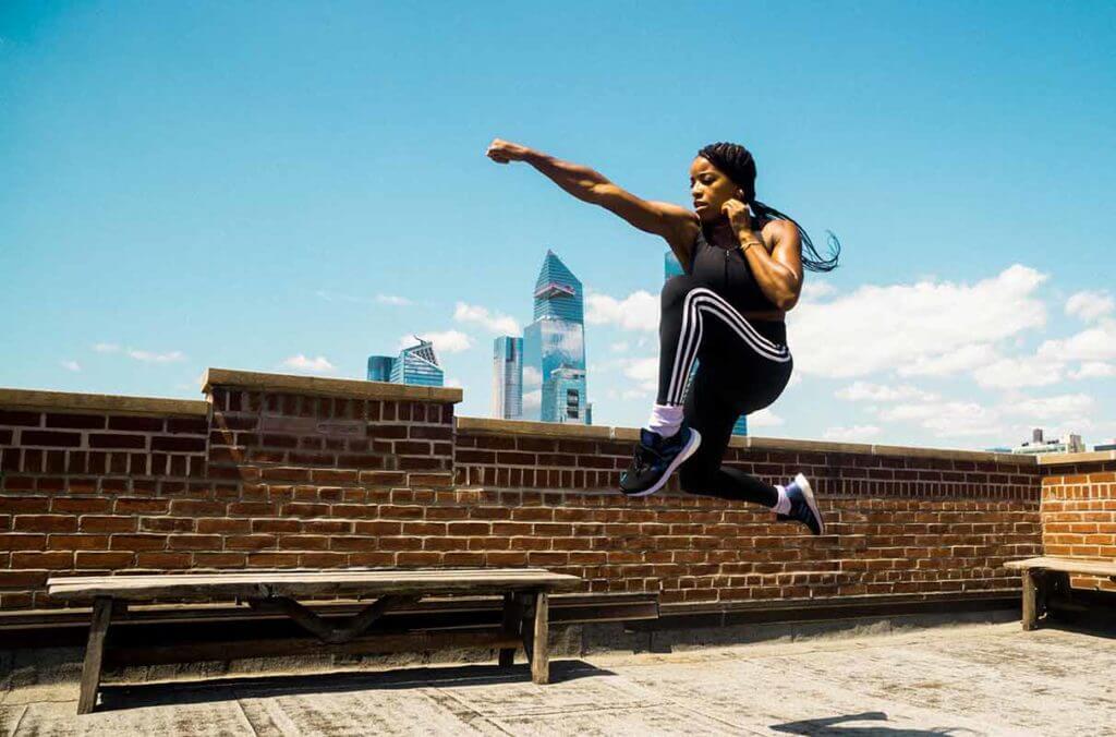 Mujer entrenando en la terraza de un edificio para ganar músculo