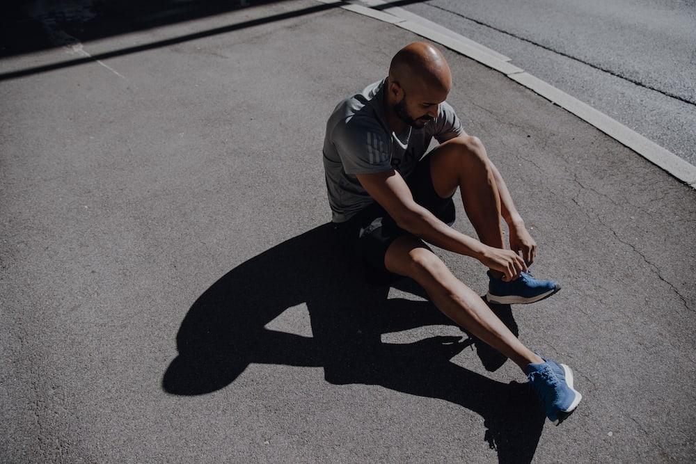 Uomo che allaccia le scarpe da corsa