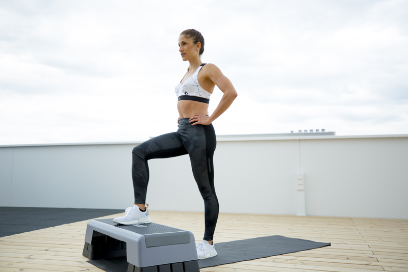 Woman is doing a step-up and lunge