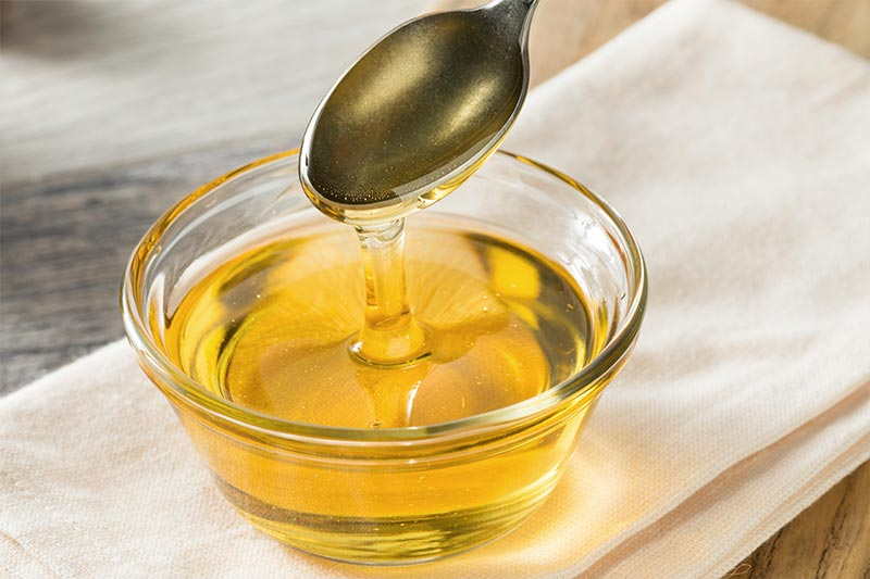 Agave syrup is dripping from a spoon