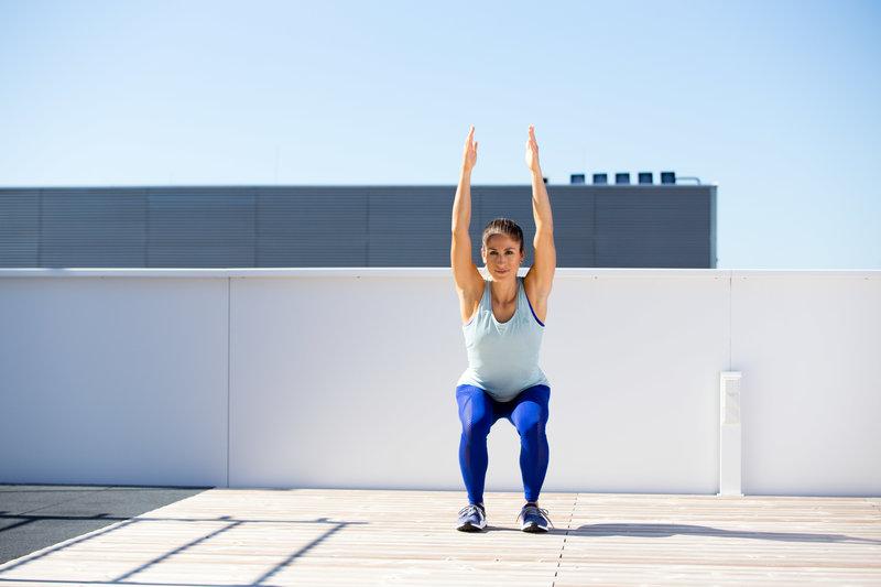 Frau macht ein Overhead Squat Assesment