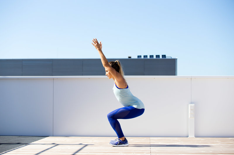 Frau macht ein Overhead Squat Assessment