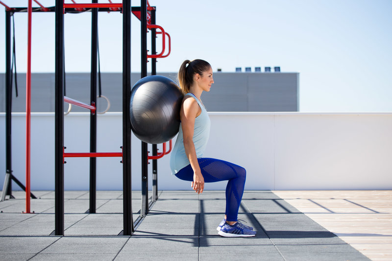 Frau macht einen Ball Squat