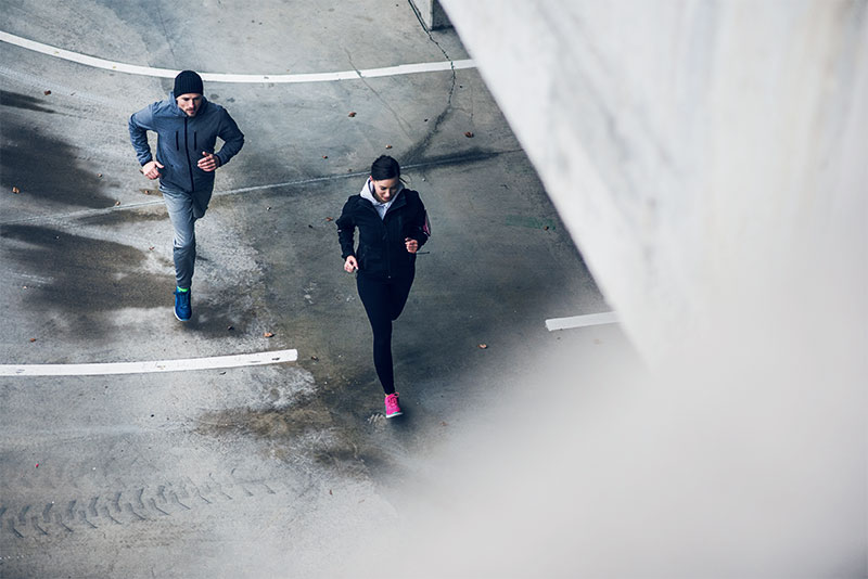 A woman and a man are running outside in the city