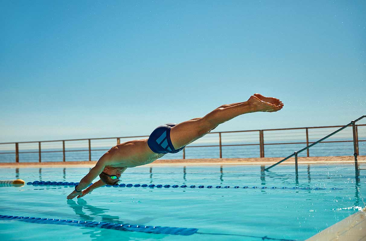 triathlete diving into water