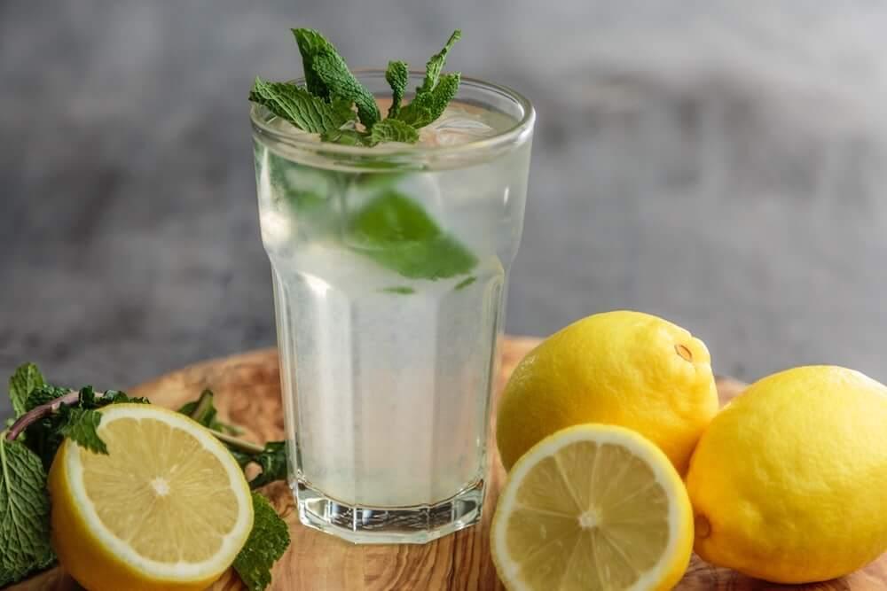 Ein Glas Zitronenwasser mit Pfefferminz-Blättern auf einem Holztablett