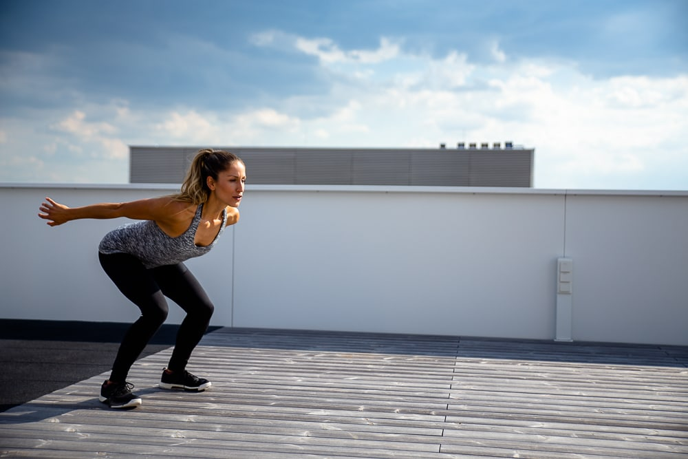 Mulher fazendo agachamento com salto