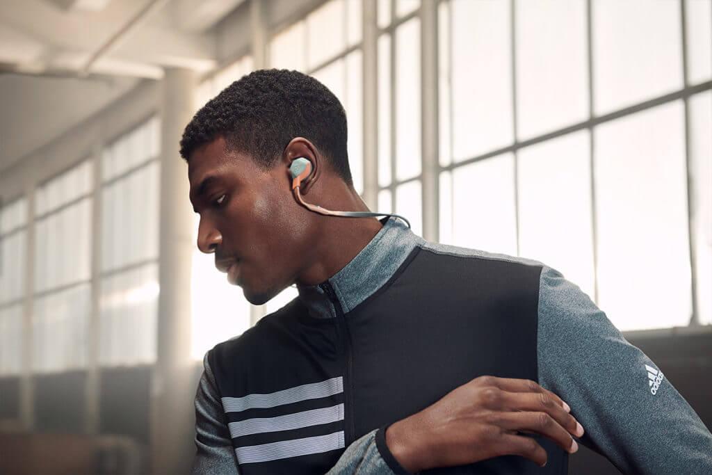 Ein junger Mann, der Musik beim Trainieren hört um seine Leistung zu steigern.