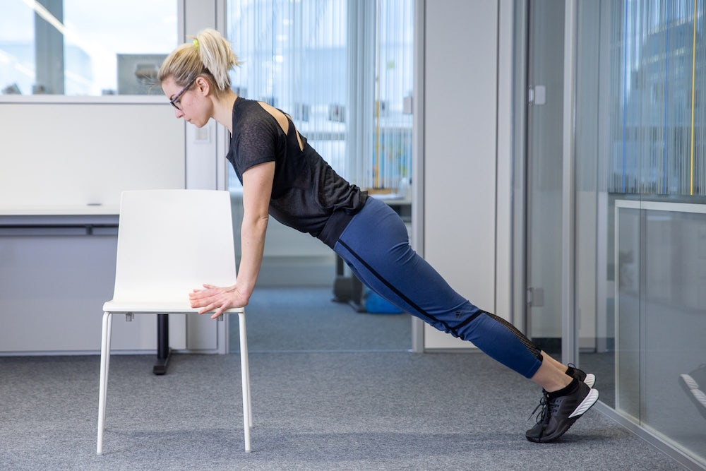 Woman doing push up on a chair