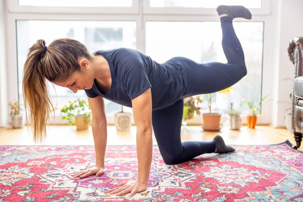 Fitness Coach Lunden Souza is doing a Donkey Kick as exercise for a better butt