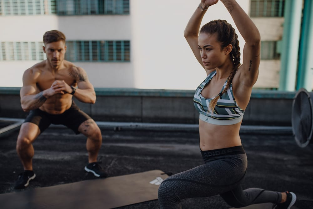 A man and a woman are training their legs with squads and lunges