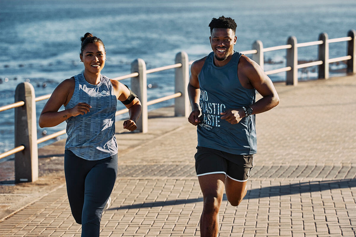 Läuferin und Läufer am Strand