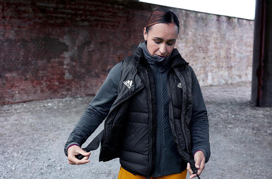 woman in warm adidas clothes prepares for running in winter