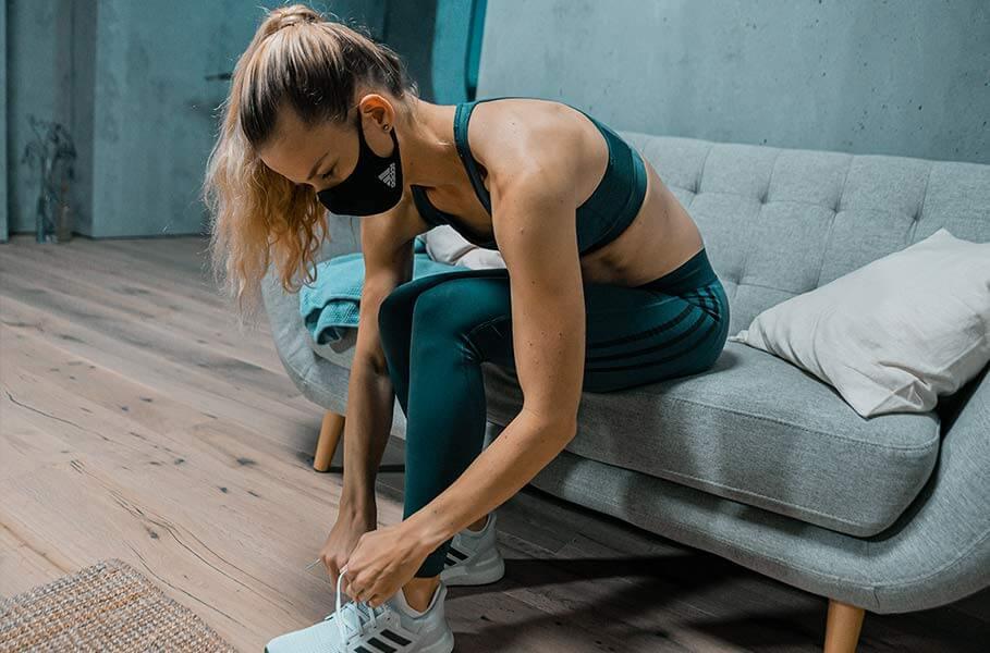 Mulher calçando o tênis para ir correr de máscara da adidas