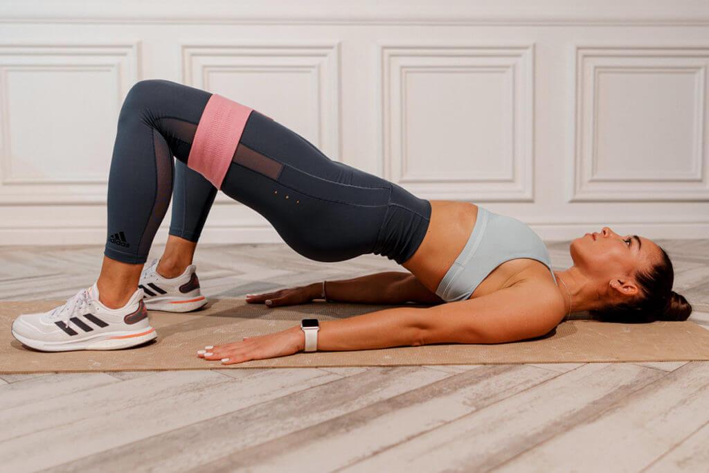 Mulher se exercitando com um elástico de resistência para aumentar a dificuldade do treino