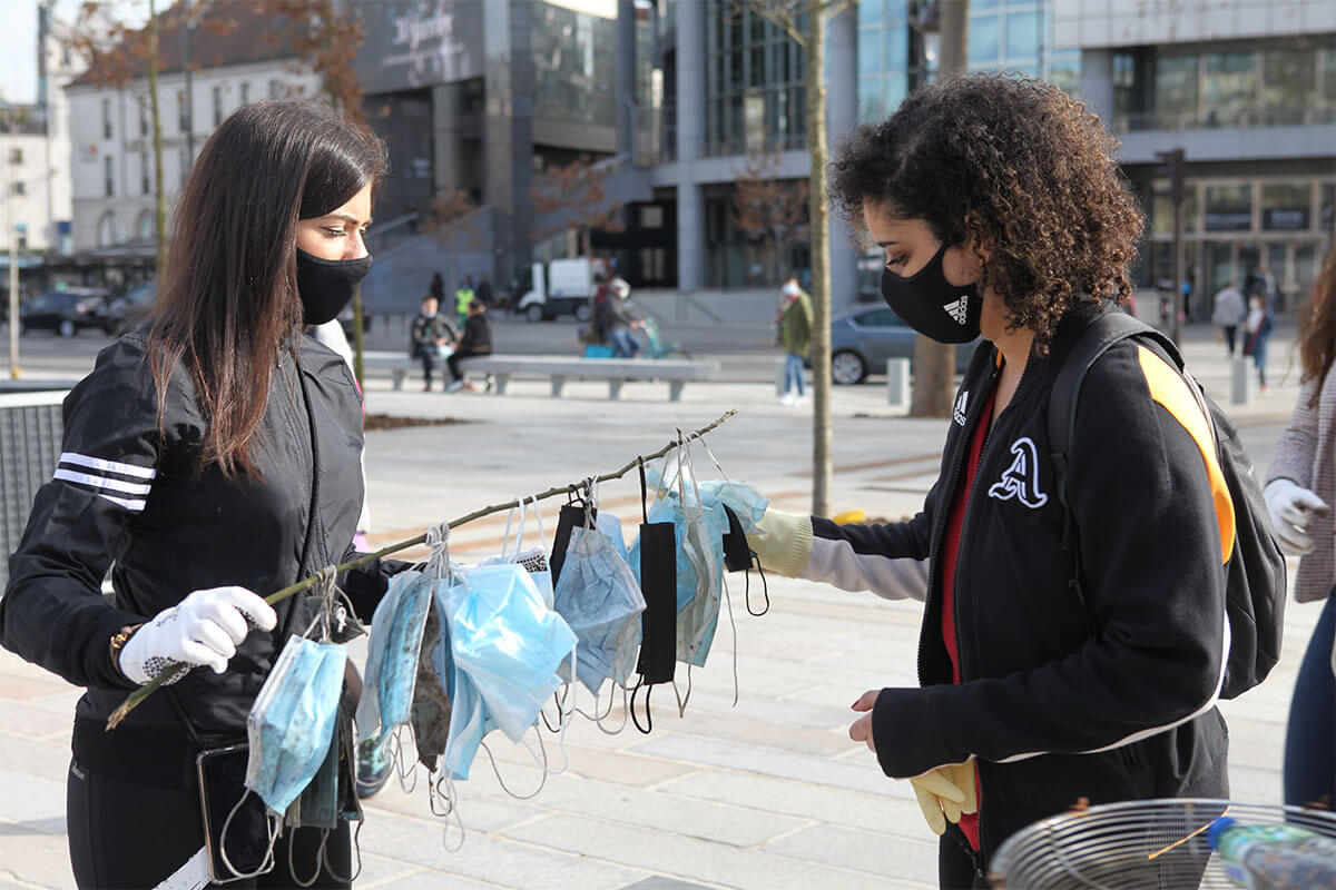 two women collecting discarded masks