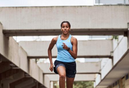 Une jeune femme court de manière concentrée