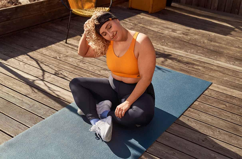 Mulhler com cara de dor fazendo yoga para relaxar e aliviar os sintomas da cólica menstrual