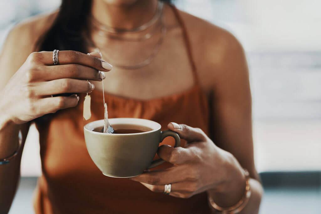 una persona prepara una tazza di tè