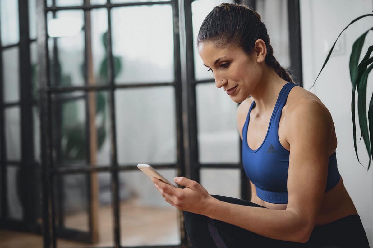 une femme consulte une appli d'entraînement à domicile