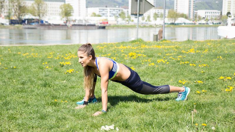 Junge Frau macht Wide Climber Jumps im Freien.