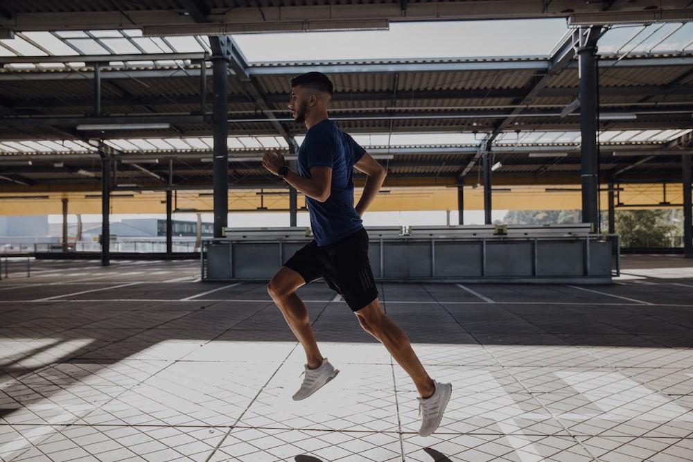 Ein junger Mann mit einem starken Oberkörper läuft durch eine Stadt