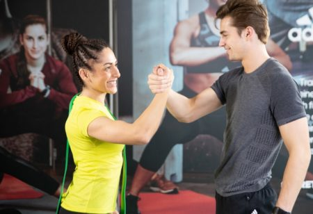 un uomo e una donna si stringono la mano dopo aver fatto esercizi per i bicipiti