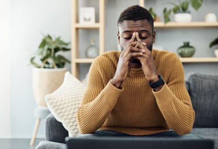 Un uomo seduto sul divano è stanco per via della depressione stagionale