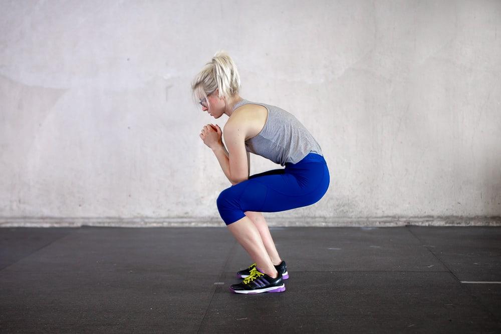woman hunching back during a squat