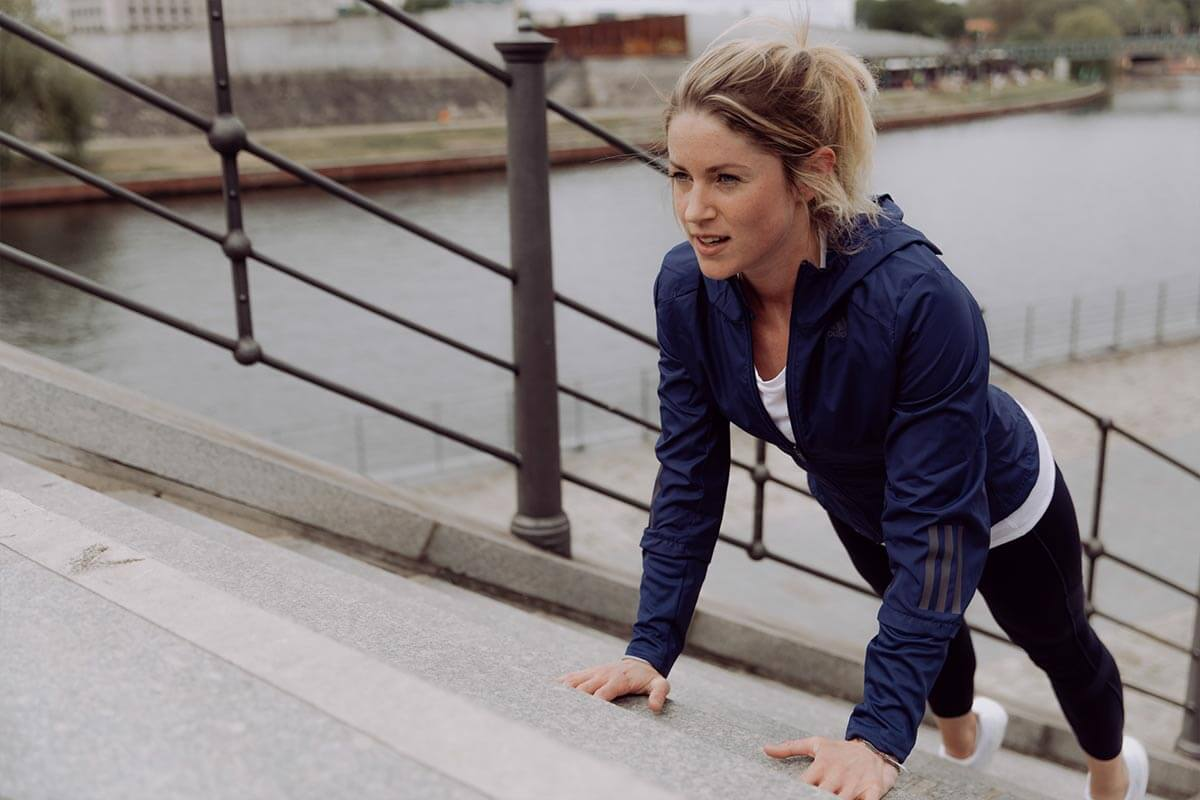 Donna si allena sulle scale vicino a un fiume