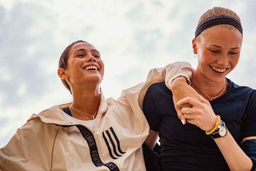 Two women during a workout laughing together and supporting each other