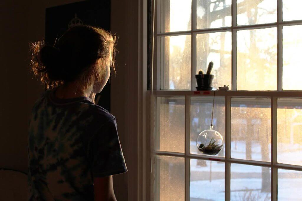 una persona guarda fuori dalla finestra prima di tornare a fare attività fisica dopo il Covid-19