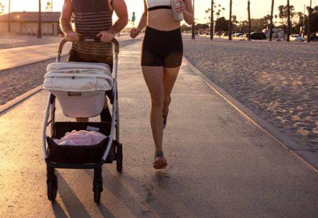 Pareja corriendo con un carrito de bebé