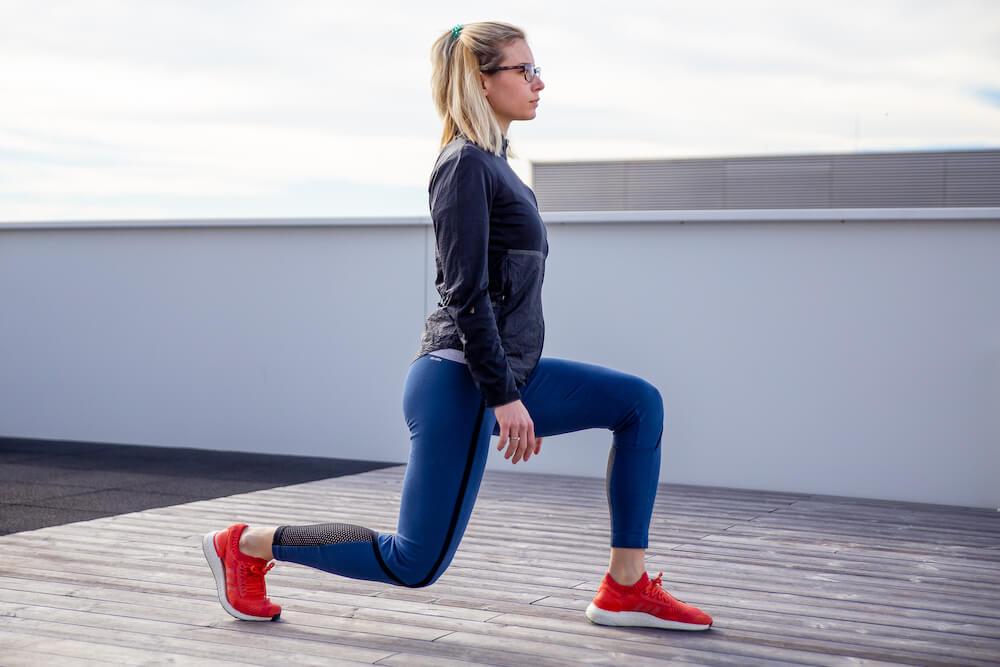 Mulher fazendo o exercício passada para a frente durante o aquecimento antes de correr