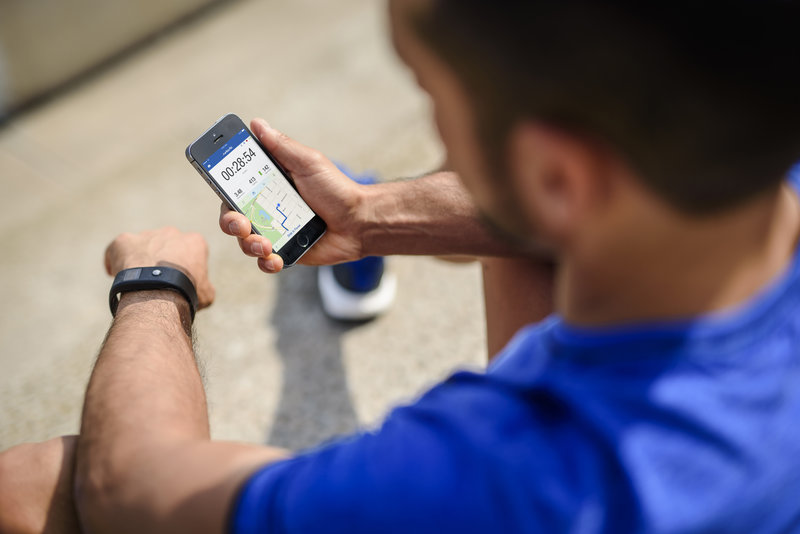 Ein Mann hält sein Smartphone in der Hand und schaut darauf