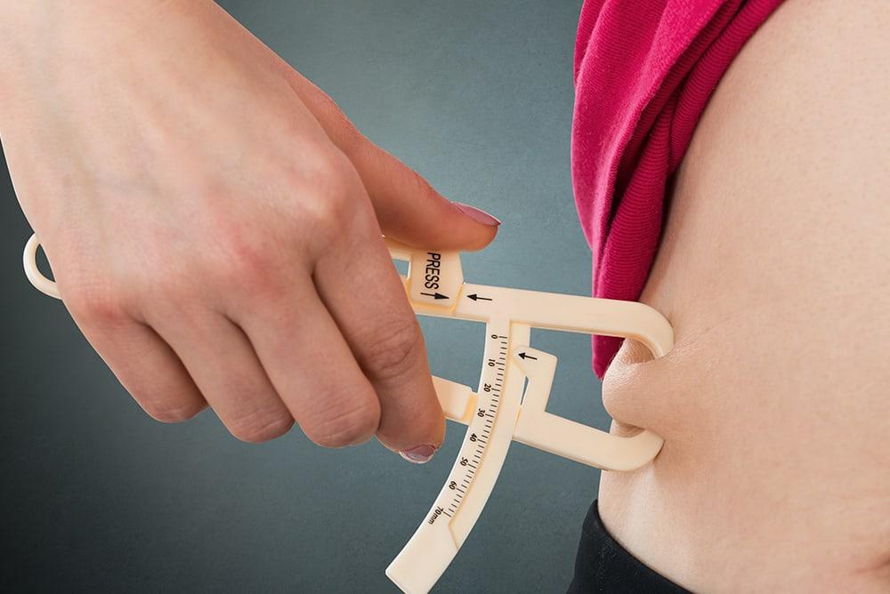 Pessoa medindo a gordura corporal com um adipômetro
