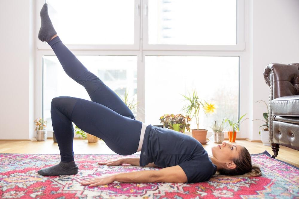 Fitness Coach Lunden Souza is doing a single leg bridge as exercise for a better butt
