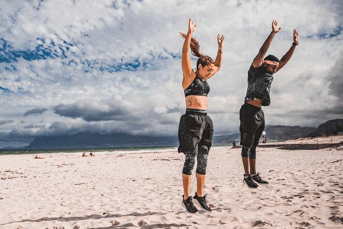 Hombre y mujer entrenando en la playa