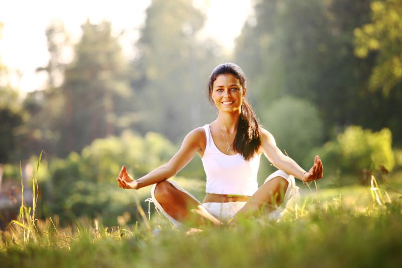 junge Frau sitzt im Gras und lächelt während ihrer Meditation