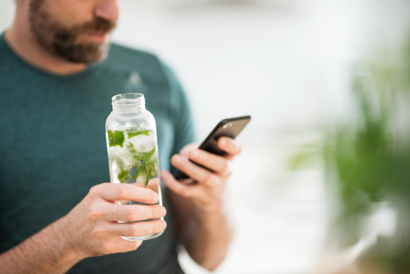 A man is holding a water bottle in one hand and his smartphone in the other hand