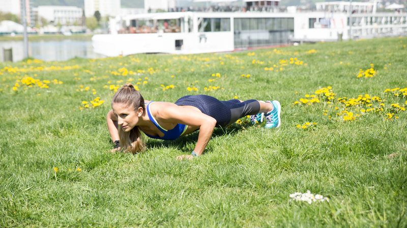 Young woman is doing Push-Up Side Planks.