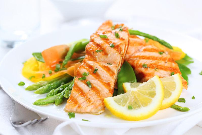 Photo d'une assiette avec des filets de saumon sur un mélange de légumes