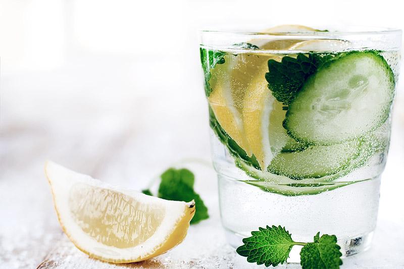 Água saborizada com rodelas de limão e pepino