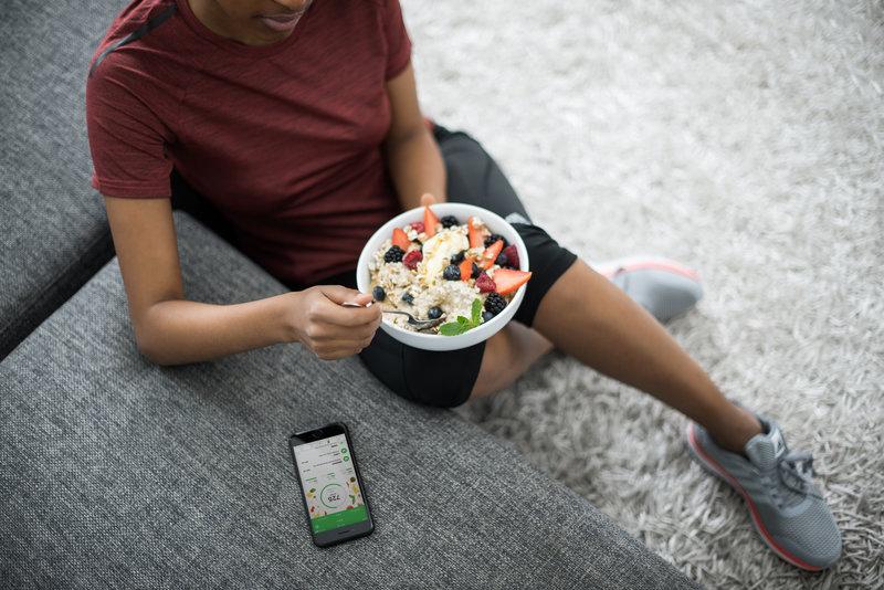 Mulher sentada sobre o tapete comendo tijela de frutas com granola