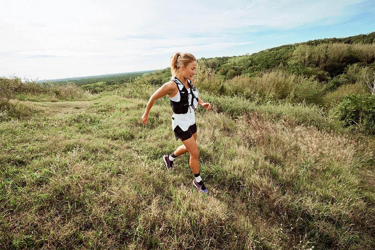 Une runner sur une route de trail