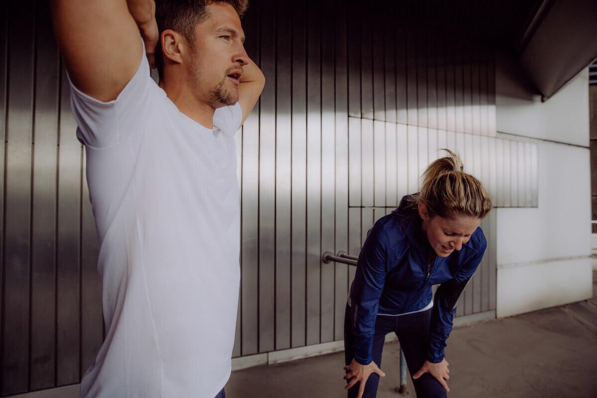 Un hombre y una mujer agotados después de una sesión de running.