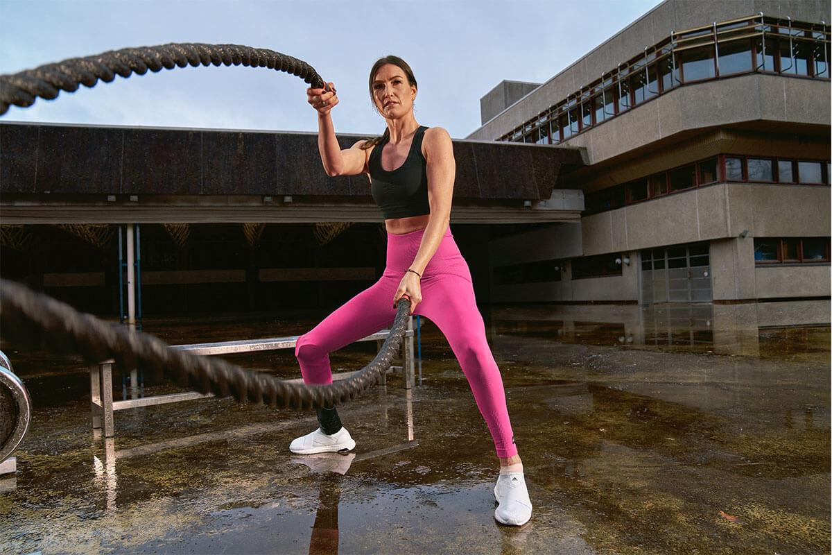 Mulher treinando com corda naval para fortalecer os braços e core