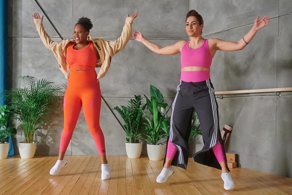 Duas mulheres fazendo polichinelos em um treino em dupla