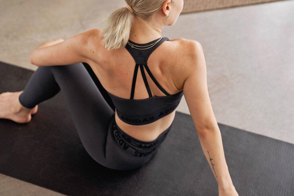 Une jeune femme s'étire sur un tapis de yoga