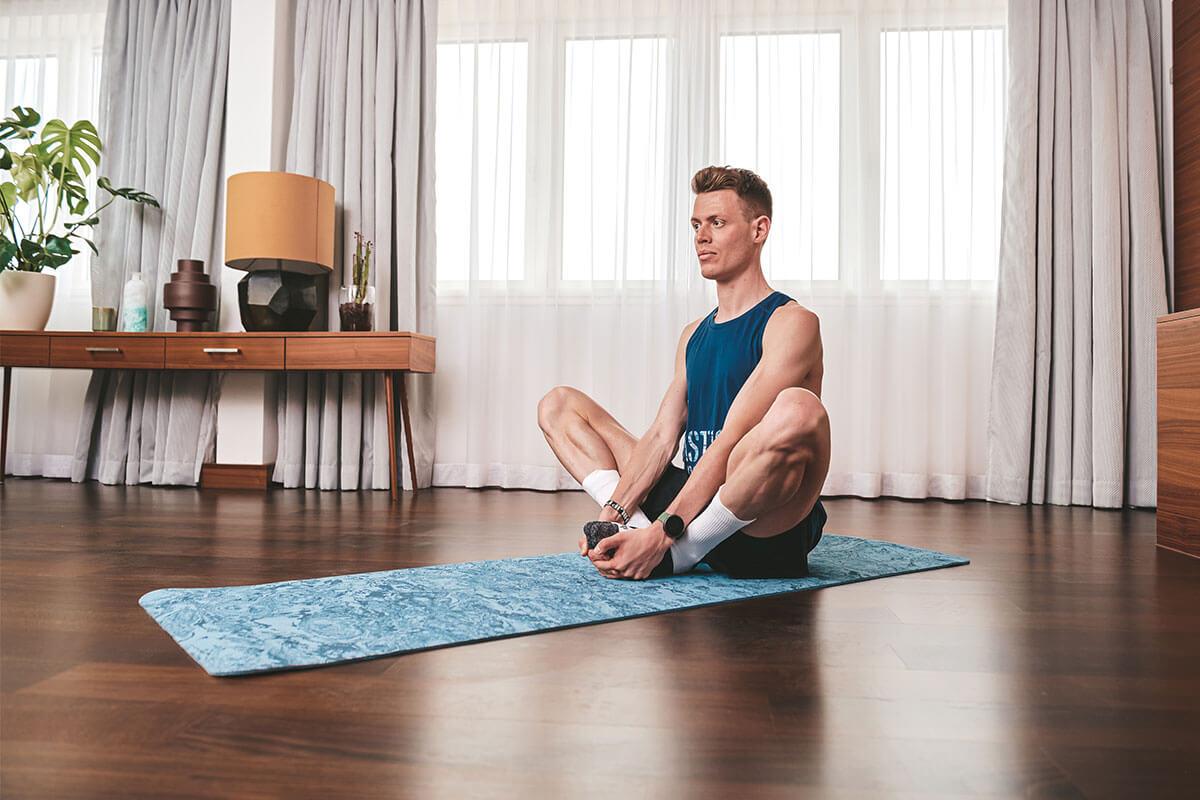Hombre haciendo estiramientos en casa para acelerar la recuperación muscular